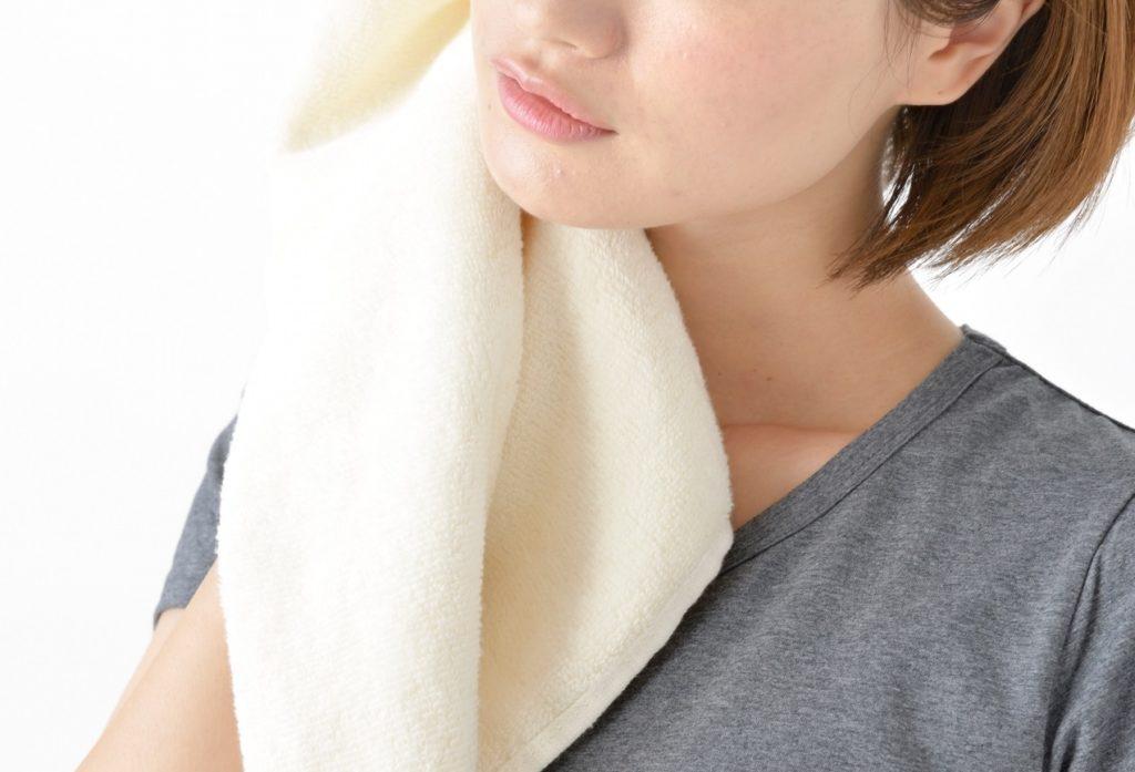 汗を拭く女性の画像