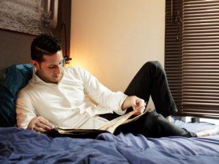 ベッドで横になり本を読む男性