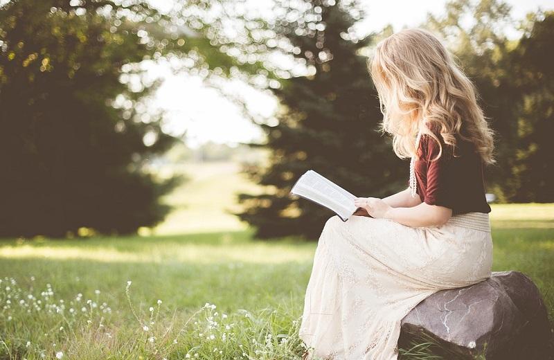 外で読書をする女の子の画像