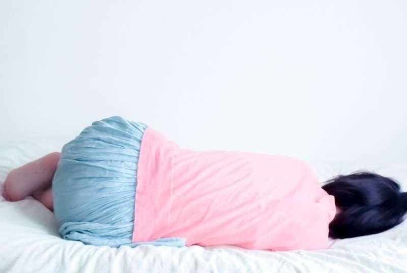 ベットで横になるピンクシャツで水色スカートの女性