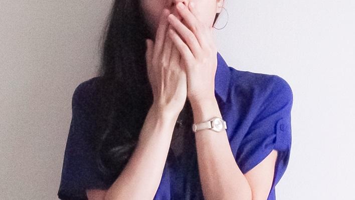 口を押える女性の画像