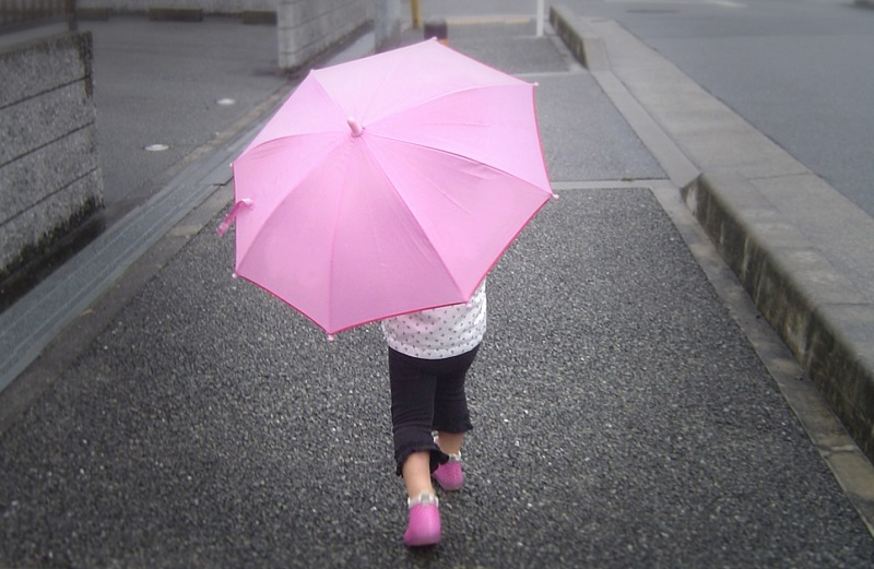 女の子がピンクの傘をさす画像