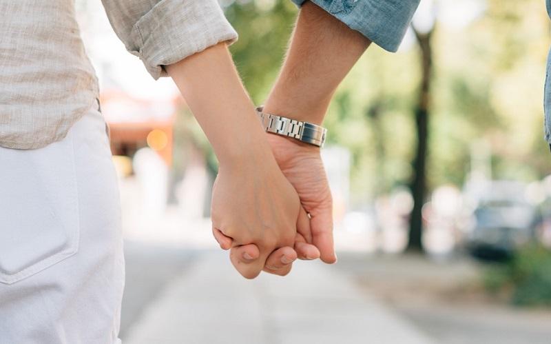 女性と男性が手をつないでいる画像