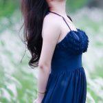 青い服を着た色白の女性が草原にたたずむ写真