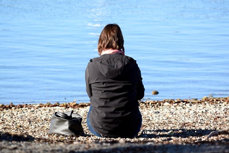 地味な女性が座る後ろ姿の画像