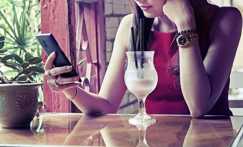 ドリンクを飲みながらスマホを操作する赤いドレスの女性の画像